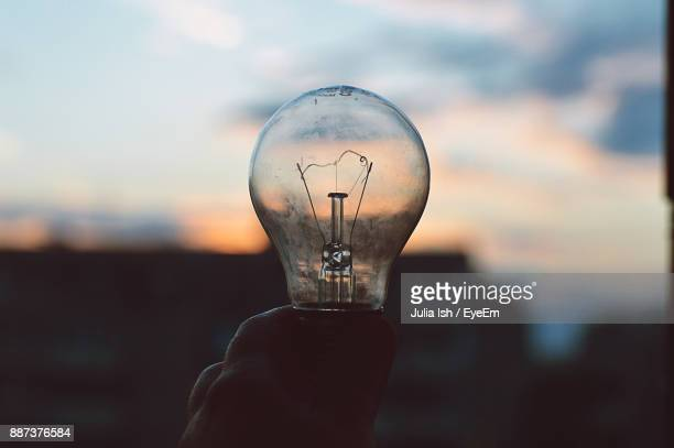 Close-Up Of Cropped Hand Holding Light Bulb Against Sky