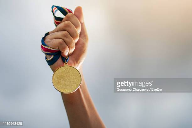 close-up of cropped hand holding medal - medalhista - fotografias e filmes do acervo