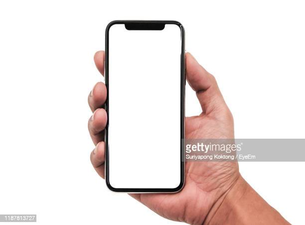 close-up of cropped hand holding mobile phone against white background - tenere foto e immagini stock