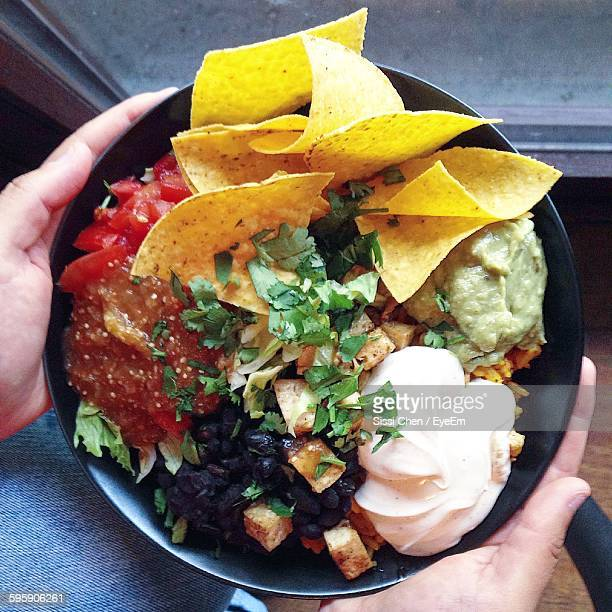 Close-Up Of Cropped Hand Holding Nachos