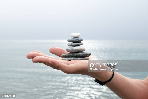 close-up of cropped hand holding pebbles - kiesel stock-fotos und bilder