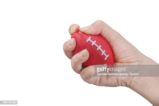 Close-Up Of Cropped Hand Holding Red Stress Ball Over White Background