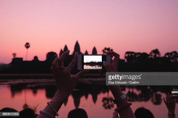 Close-Up Of Cropped Hand Photographing Angkor Wat By Lake At Sunset