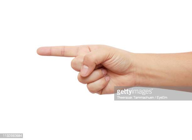 close-up of cropped hand pointing against white background - pointing stock pictures, royalty-free photos & images