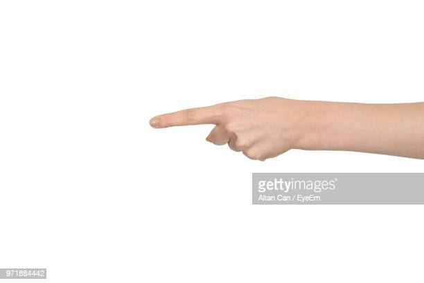 close-up of cropped hand pointing finger over white background - pointing stock photos and pictures