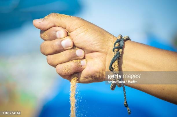 close-up of cropped hand pouring sand - bracelet stock pictures, royalty-free photos & images