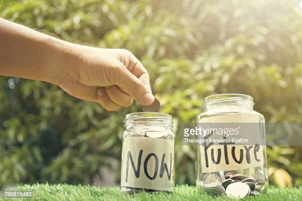 close-up of cropped hand putting money in jar - saving stock pictures, royalty-free photos & images