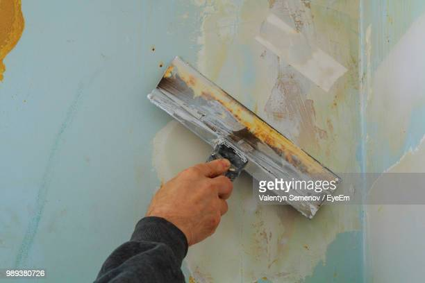 close-up of cropped hand scraping paint on wall - scraping stock photos and pictures