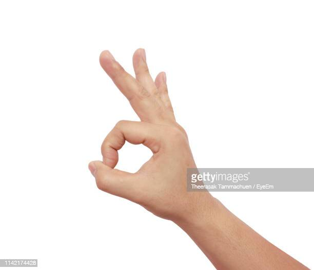 close-up of cropped hand showing ok sign against white background - ok sign stock pictures, royalty-free photos & images