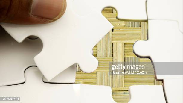 Close-Up Of Cropped Hand Solving Jigsaw Puzzle