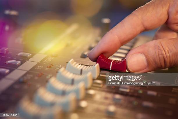 Close-Up Of Cropped Hand Using Sound Mixer