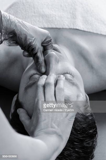 Close-Up Of Cropped Hands Giving Massage To Man