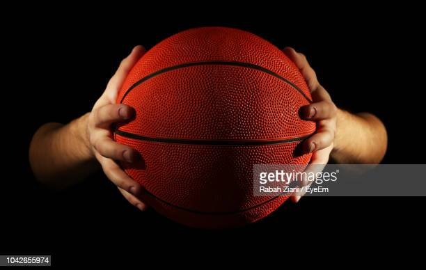 close-up of cropped hands holding basketball against black background - basketball stock-fotos und bilder
