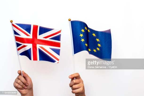 close-up of cropped hands holding british and european union flag against white wall - britse vlag stockfoto's en -beelden