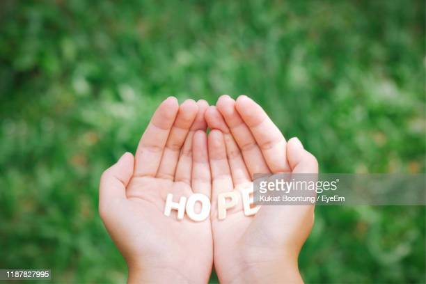 close-up of cropped hands holding hope text - single word stock pictures, royalty-free photos & images