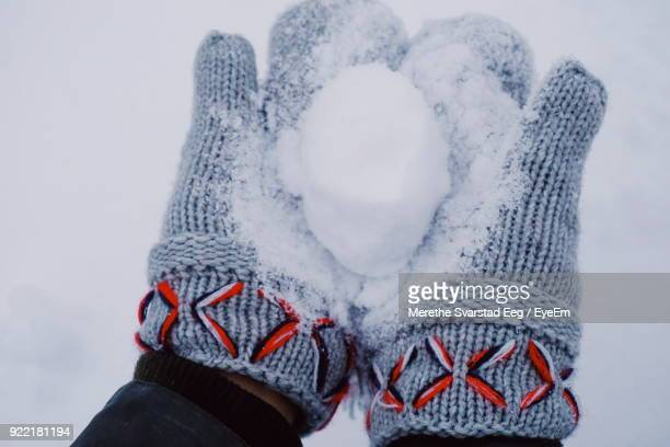 close-up of cropped hands holding snowball - mitten stock photos and pictures