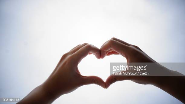 close-up of cropped hands making heart shape against clear sky - coeur photos et images de collection