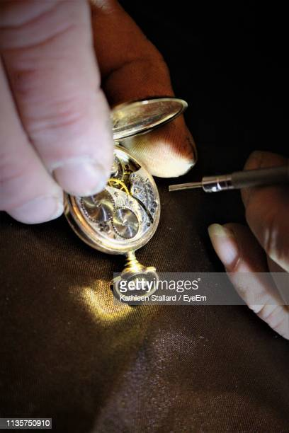 close-up of cropped hands repairing pocket watch - broken arrow oklahoma stock photos and pictures