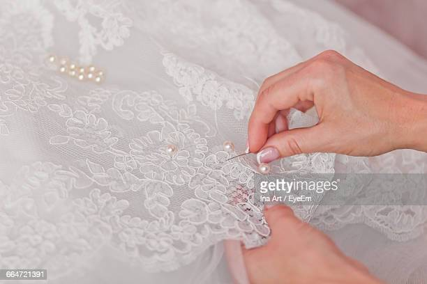 Close-Up Of Cropped Hands Sewing Wedding Dress