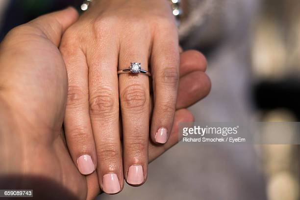 close-up of cropped hands with wedding ring - diamond ring stock pictures, royalty-free photos & images