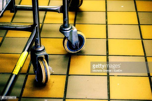 Close-Up Of Cropped Shopping Trolley On Tiled Floor