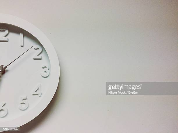 Close-Up Of Cropped Wall Clock Over White Background