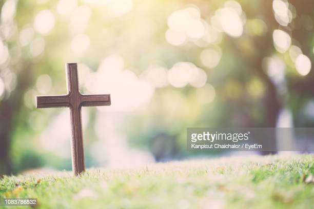 close-up of cross in cemetery - cemetery stock pictures, royalty-free photos & images