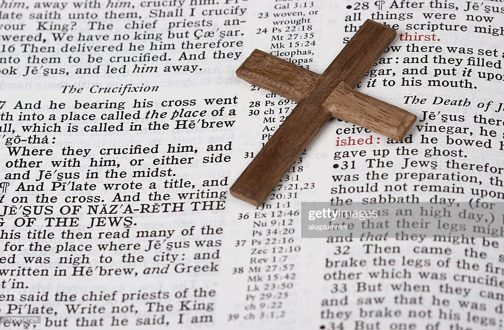 Closeup Of Cross On Bible Open To Crucifixion Passage Stock