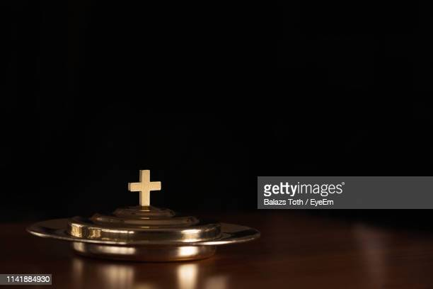 close-up of cross on metal at table against black background - easter cross stock pictures, royalty-free photos & images
