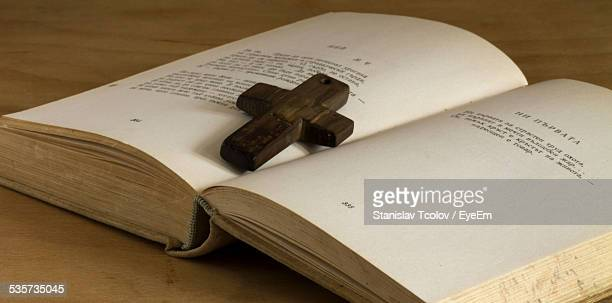 Close-Up Of Cross On Open Book