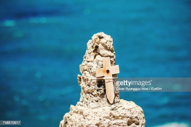 Close-Up Of Cross On Rock Formation By Sea In Sunny Day