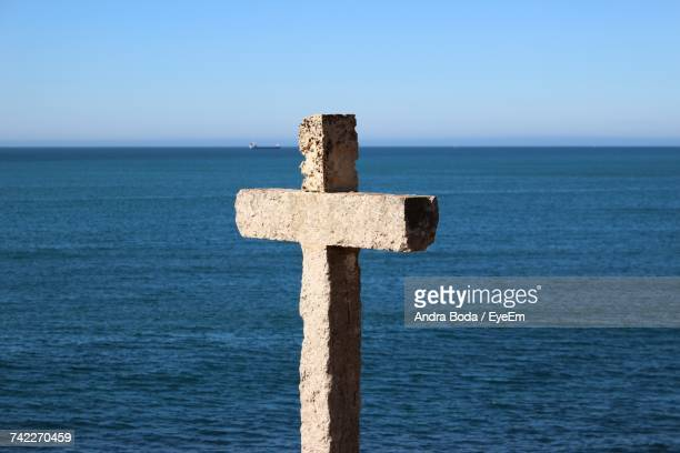 close-up of cross on sea against clear sky - crucifix stock pictures, royalty-free photos & images