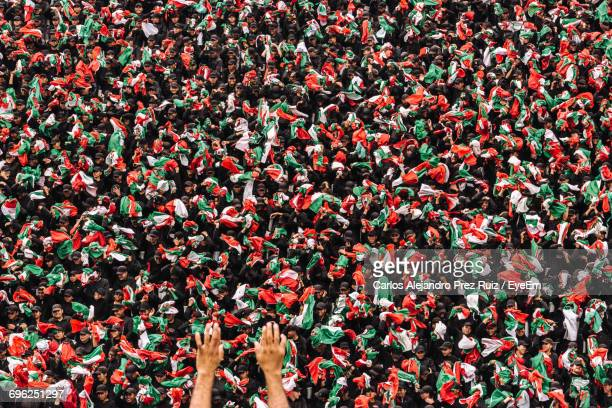 close-up of crowd holding mexican flags - bandera mexicana fotografías e imágenes de stock