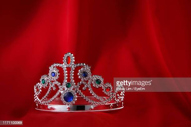 close-up of crown against red fabric - crown close up stock pictures, royalty-free photos & images