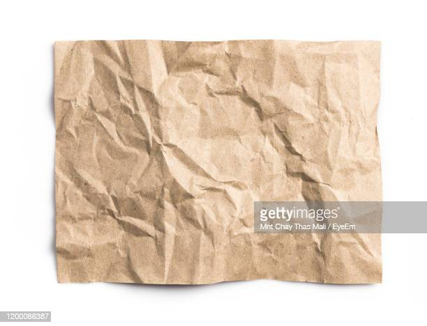 close-up of crumpled brown paper against white background - brown paper stock pictures, royalty-free photos & images