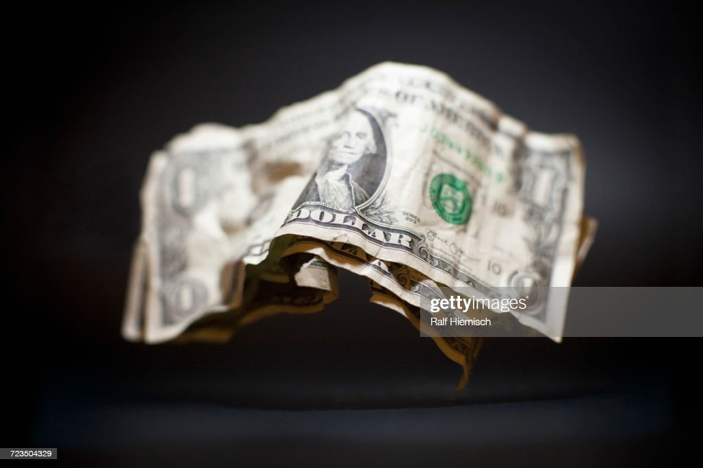 Close-up of crumpled old American one dollar bills levitating against black background : Stockfoto