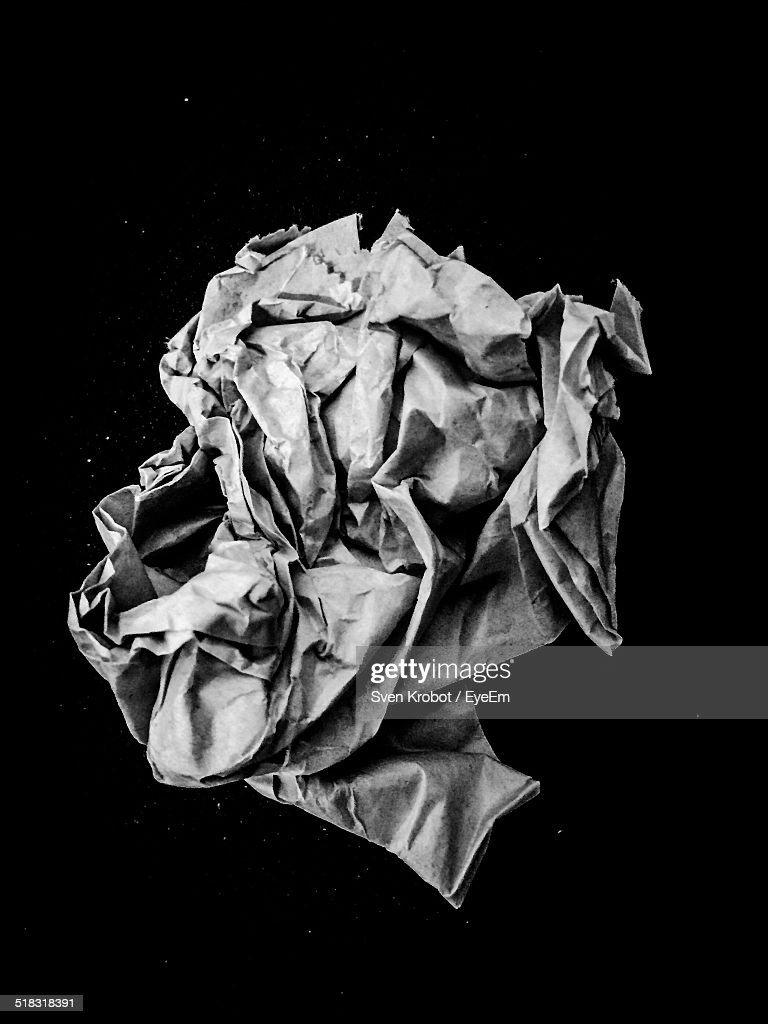 Close-up Of Crumpled Paper Against Black Background : Stock Photo
