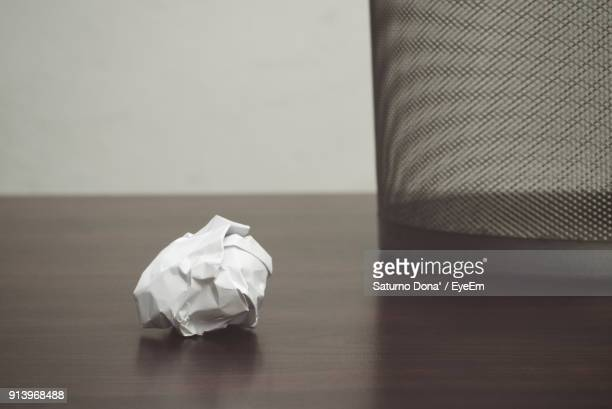 Close-Up Of Crumpled Paper And Garbage Can On Table