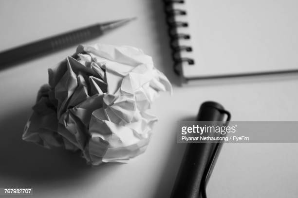 Close-Up Of Crumpled Paper Ball Over White Table