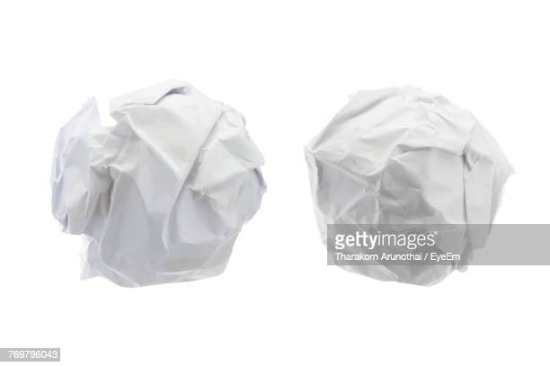 Close-Up Of Crumpled Papers Over White Background