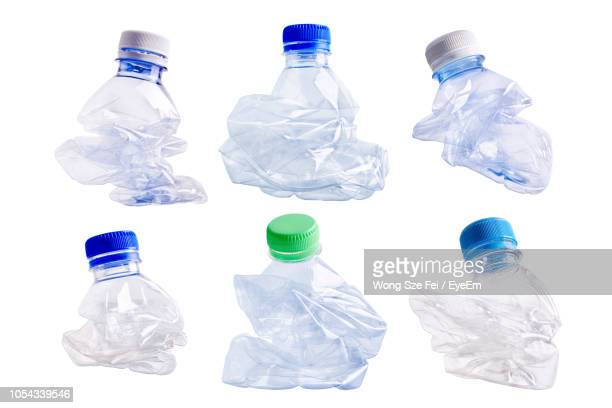 close-up of crushed bottles over white background - crushed stock pictures, royalty-free photos & images