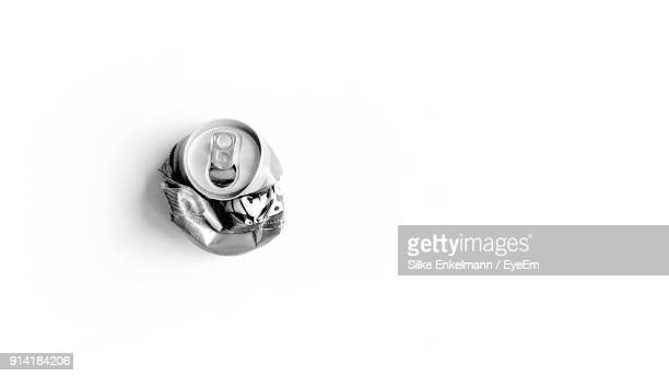 close-up of crushed can over white background - crush foto e immagini stock