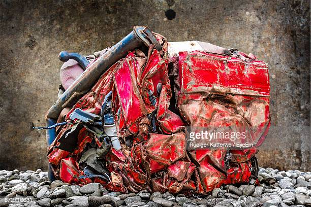 Close-Up Of Crushed Red Car At Junkyard