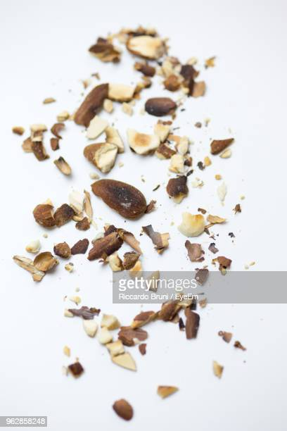 close-up of crushed roasted almonds white background - nutshell stock photos and pictures