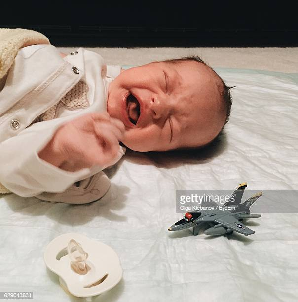 Close-Up Of Crying Baby With Airplane Toy On Bed