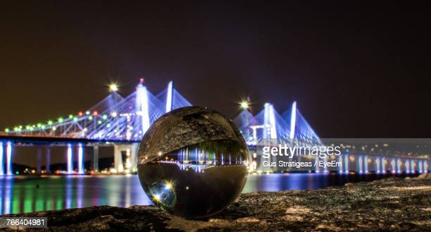 close-up of crystal ball against illuminated cable-stayed bridge at night - tarrytown stock photos and pictures