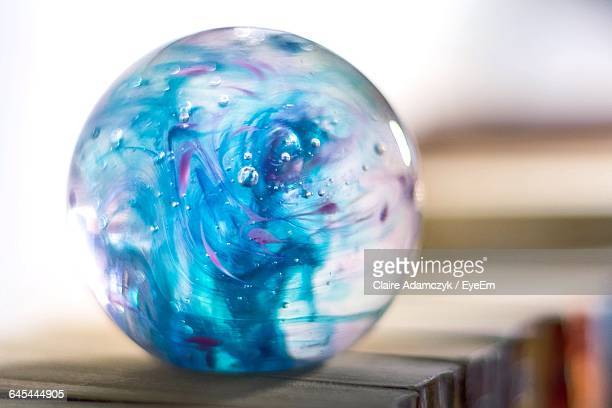 Close-Up Of Crystal Ball On Book