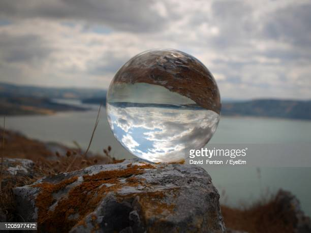 close-up of crystal ball on rock against sky - llandudno wales stock pictures, royalty-free photos & images
