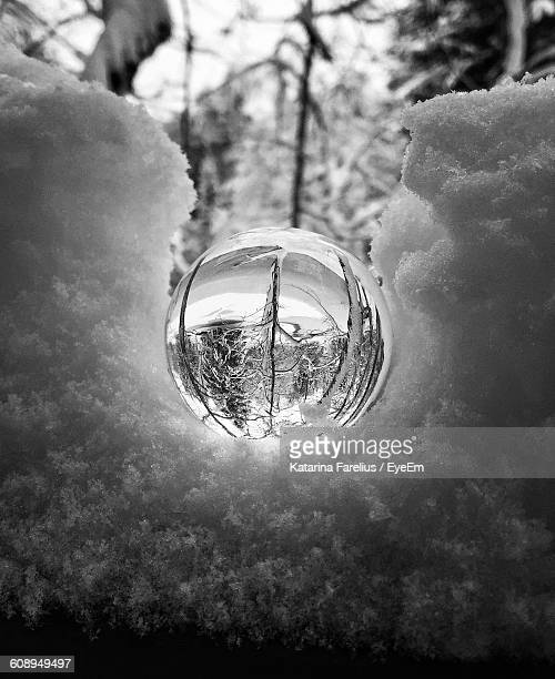 Close-Up Of Crystal Ball With Reflection On Snow