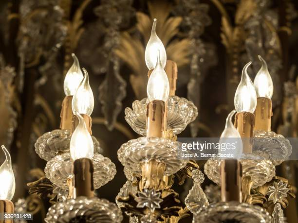 Close-up of crystal chandelier of classic style with the flushed lights. High resolution photography.